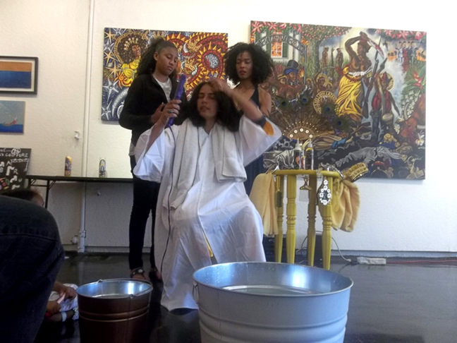 Audience members, Claudia Jones and Kenturah Davis, heat straightening my hair with a hot comb and flat iron