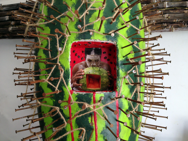 Detail of Ain't Funny Crucifix 96″x72″x36″, Purple Sugar Cane, Conga Drum, Nails, Rope, Acrylic Paint, Watermelon Seeds, Digital Photograph © 2014 by Lili Bernard