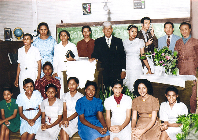 My grandfather, Rev. José Rodríguez Figueroa with his congregation at the church he pastored in his house, circa 1938, Santiago de Cuba, Cuba. My dad is the boy in white, standing to the far left, with his tongue sticking out and his eyes crossed. My grandfather, with the white hair, is sandwiched between his two daughters, my two aunts, beside whom is his wife, my grandmother, to the left. My other two aunts  are pictured in the bottom row, one farthest to the right, the other, second from the left.